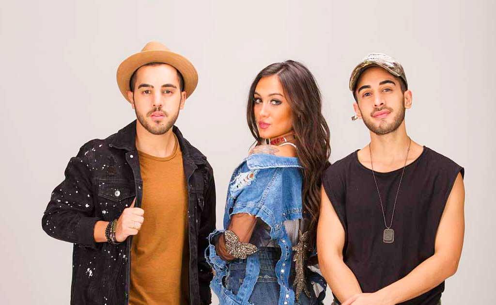 três pessoas dois homens uma mulher homem com chapéu homem com boné mulher com roupa jeans integrantes da banda melim